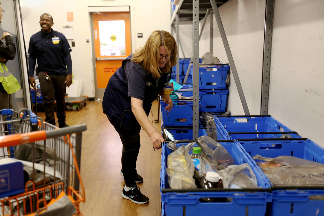 Walmart Associate Molly preps carts for online pickup orders in the online grocery pickup room ...