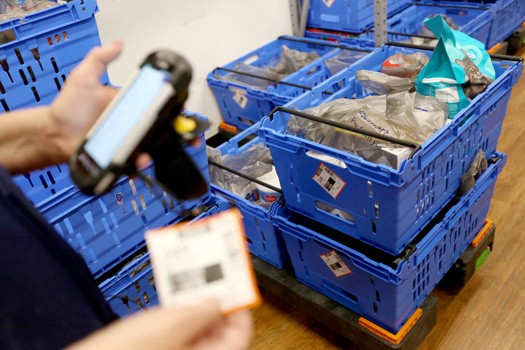 Walmart Associate Molly scans a cart for an online pickup order in the online grocery pickup ro ...