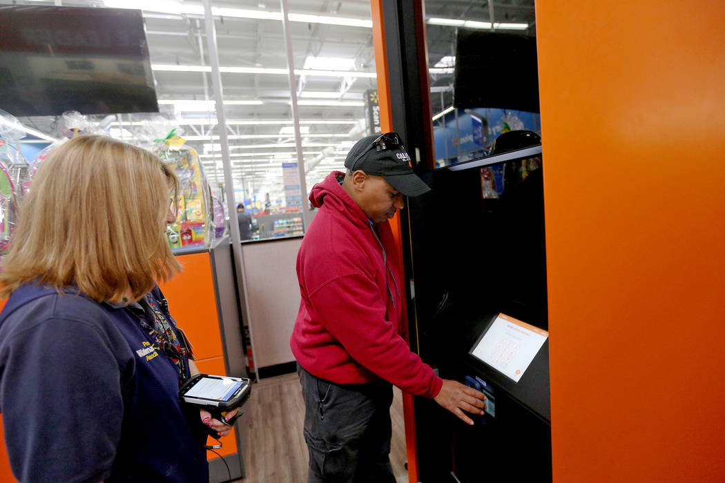 Walmart Associate Molly watches Harold Lloyd scan for his order at the pickup tower at the Walm ...