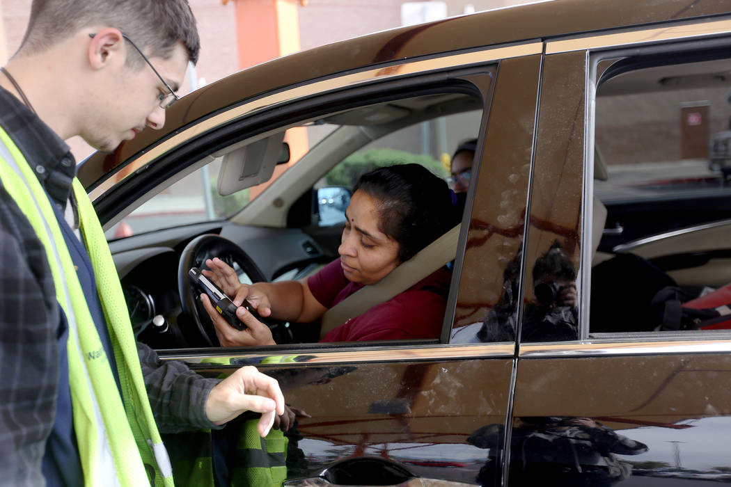 Walmart Associate Dharian H. asks Dr. Rekha Subramania to sign for her online order at a pickup ...