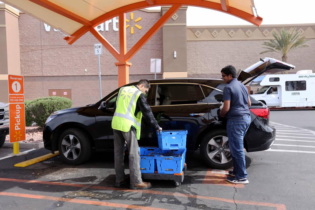 Walmart Associate Dharian H. helps Aditya Subramania, 17, load his family's online order at a p ...
