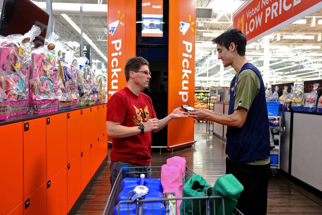 Harold Lloyd signs his order for Walmart Associate Tye Bonilla scan at the pickup tower at the ...