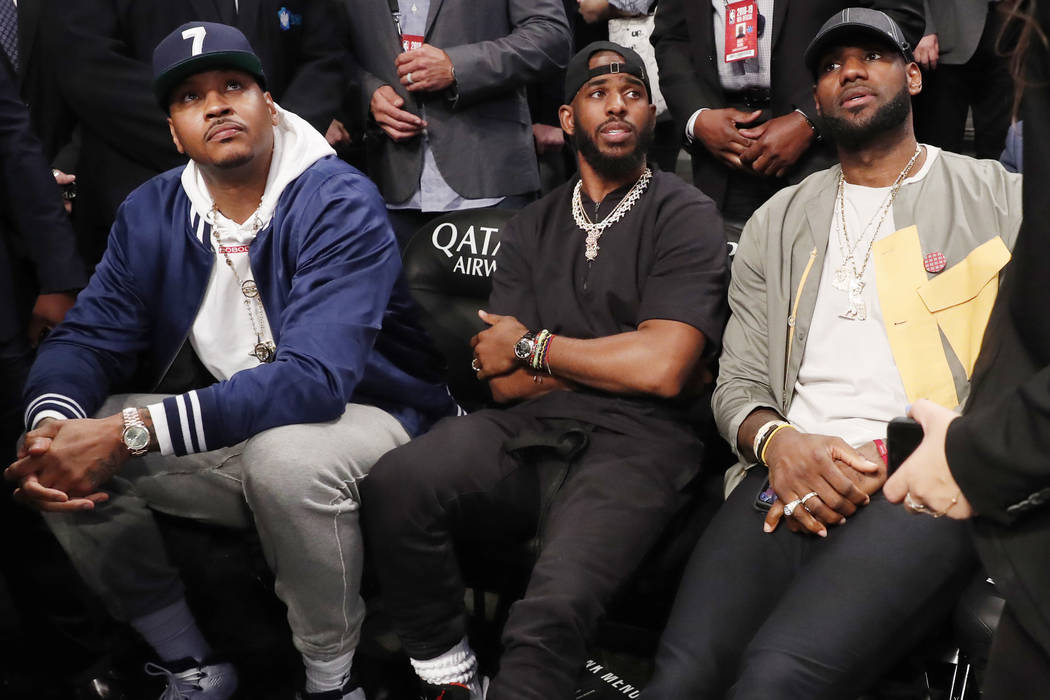Carmelo Anthony, Chris Paul and LeBron James, from left, watch during the first half of an NBA ...
