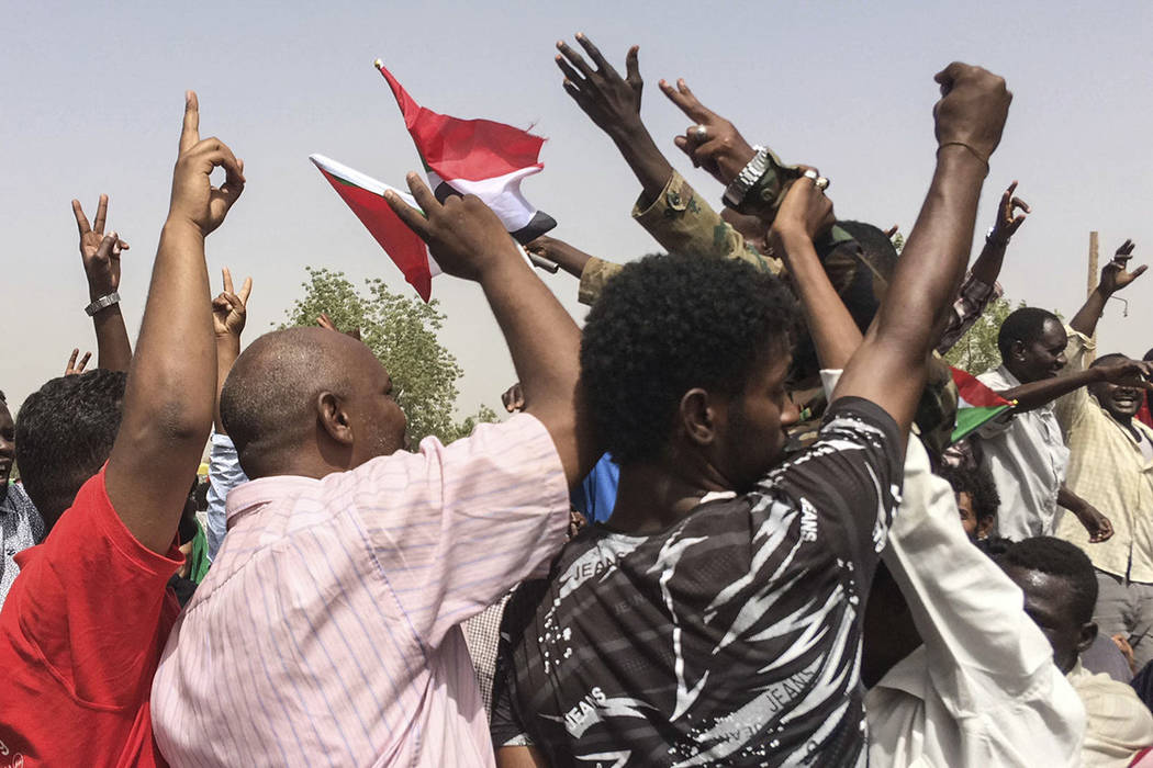 Sudanese celebrate after officials said the military had forced longtime autocratic President O ...