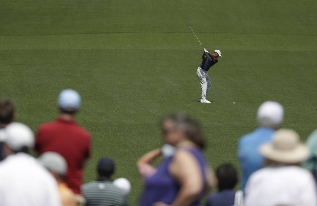 Tiger Woods hits on the eighth hole during the first round for the Masters golf tournament Thur ...