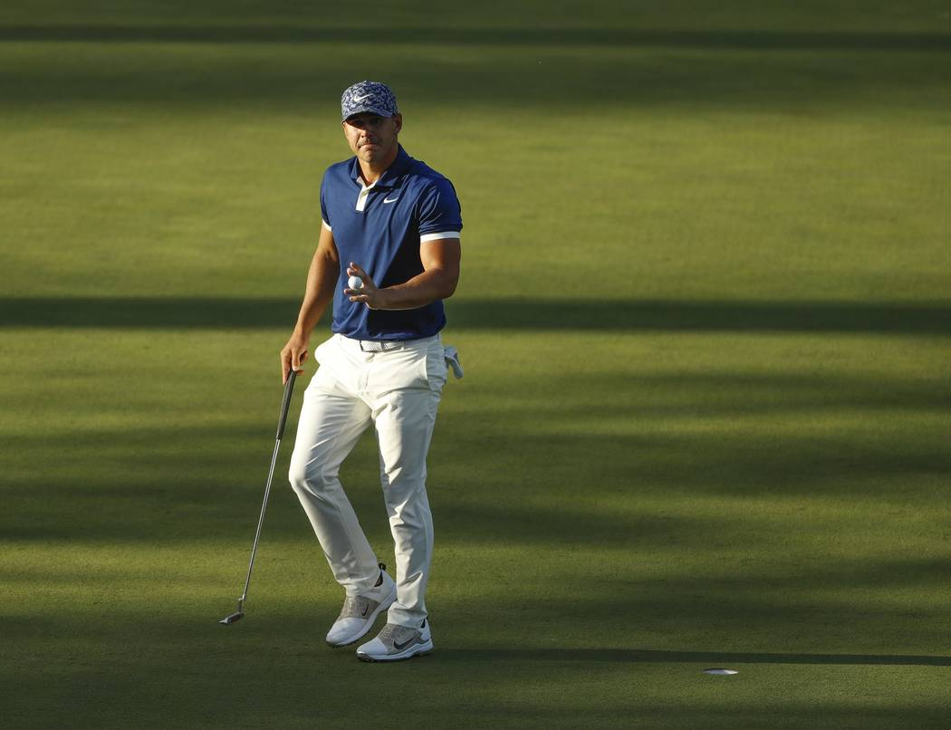 Brooks Koepka reacts after his putt on the 15th hole during the first round for the Masters gol ...