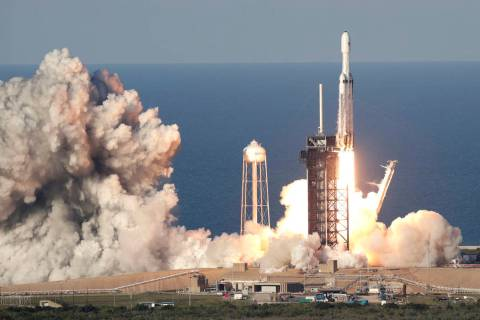 A SpaceX Heavy rocket carrying a communication satellite lifts off from pad 39A at the Kennedy ...