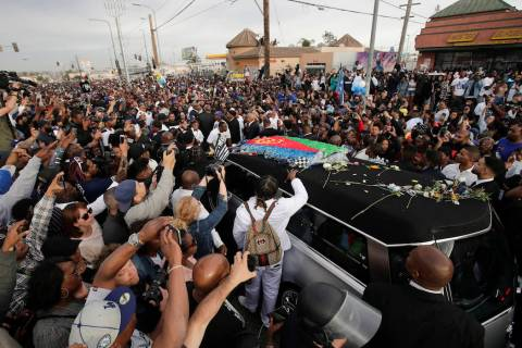 A hearse carrying the casket of slain rapper Nipsey Hussle passes through the crowd Thursday, A ...