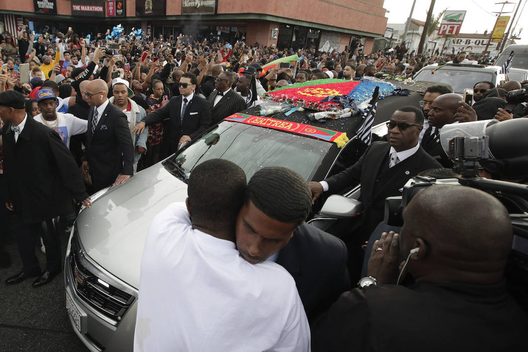Two men hug as a hearse carrying the casket of slain rapper Nipsey Hussle passes through the cr ...