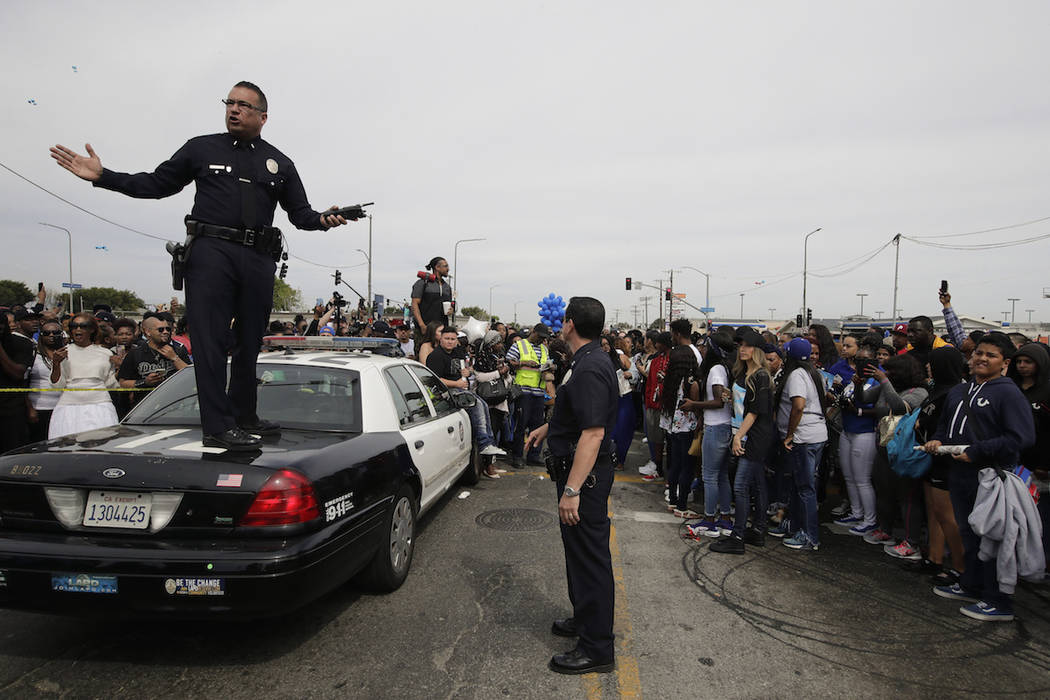 Los Angeles police officers tell the crowd to back up to clear the way for a hearse carrying th ...