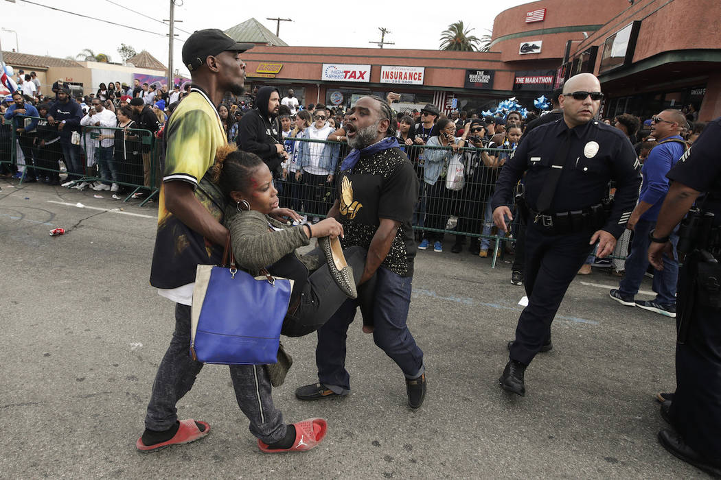 Two men carry a woman injured in stampede as people gather to watch a hearse carrying the caske ...