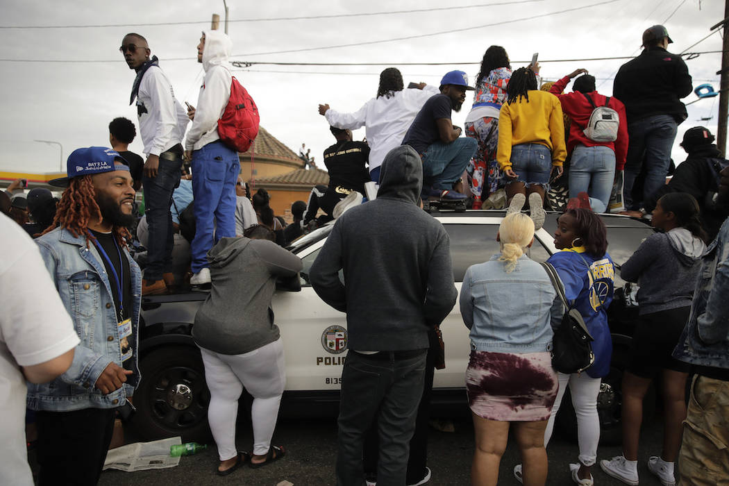 People climb on a police vehicle to watch a hearse carrying the casket of slain rapper Nipsey H ...