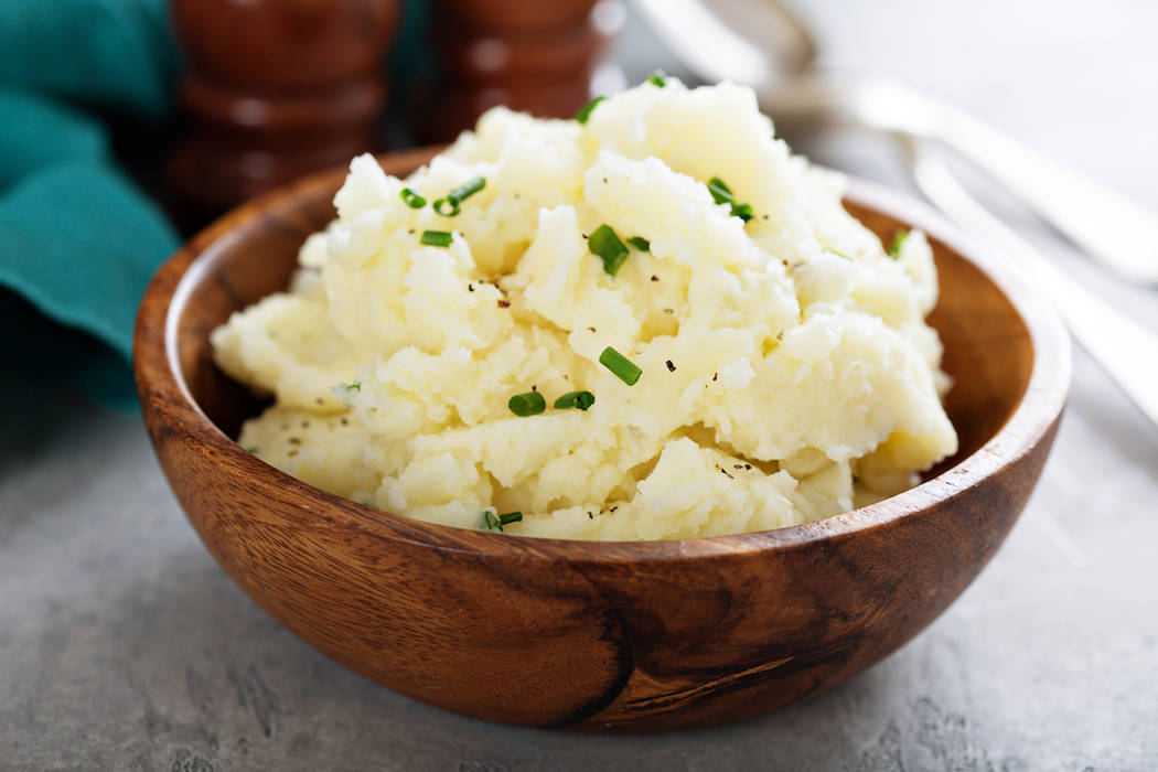 Fluffy mashed potatoes with chives in a wooden bowl (Getty Images)