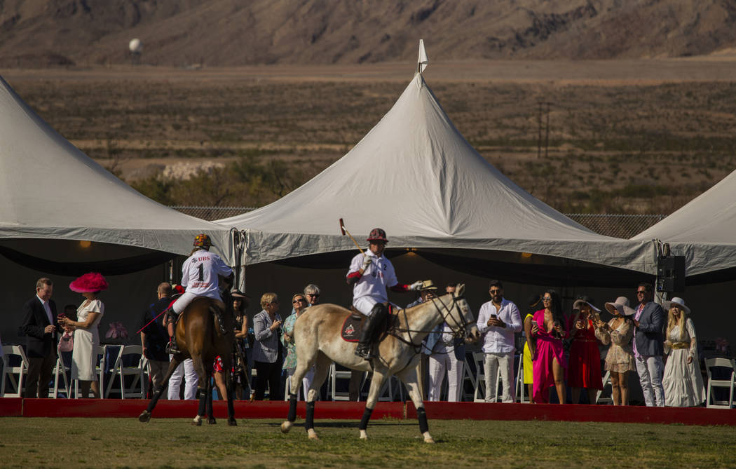 Polo players from UBS Financial Services and Blue Heronshow off their horses to the guests duri ...