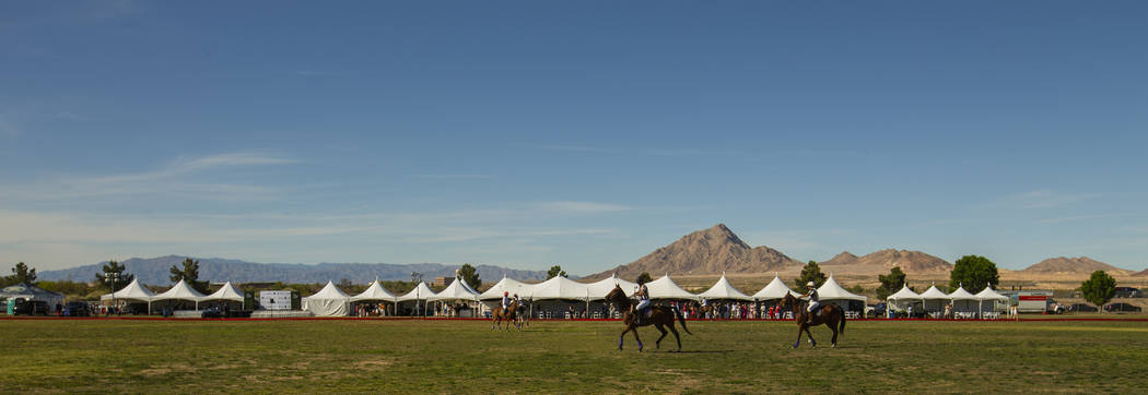 Players from UBS Financial Services and Blue Heron race up the field during the Las Vegas Polo ...