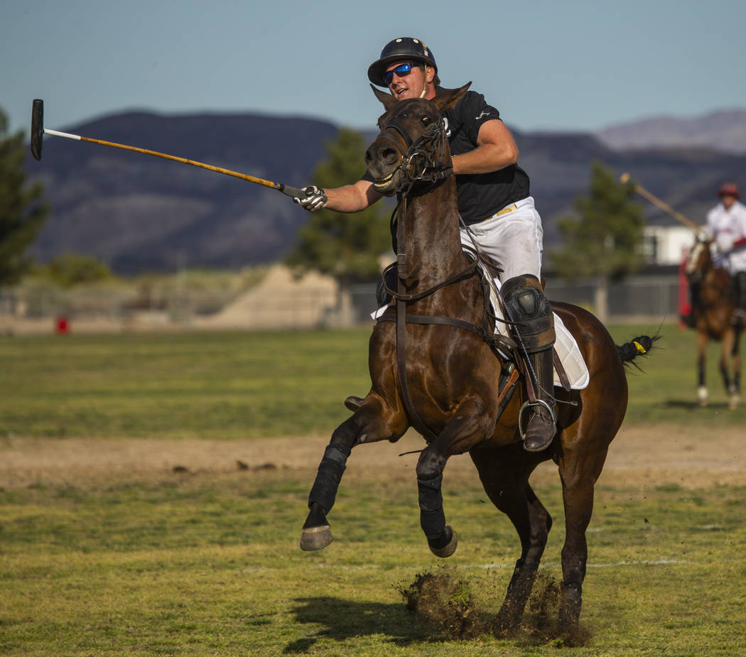 Blue Heron's Dan Faherty (2) sends the ball up the field as his horse leaps versus UBS Financia ...