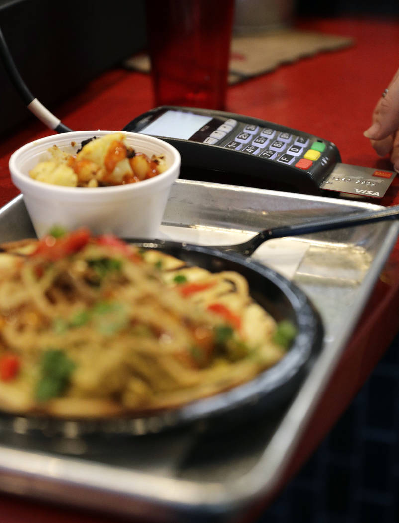 FILE - In this April 10, 2018, file photo, a customers uses a credit card machine to pay for fo ...