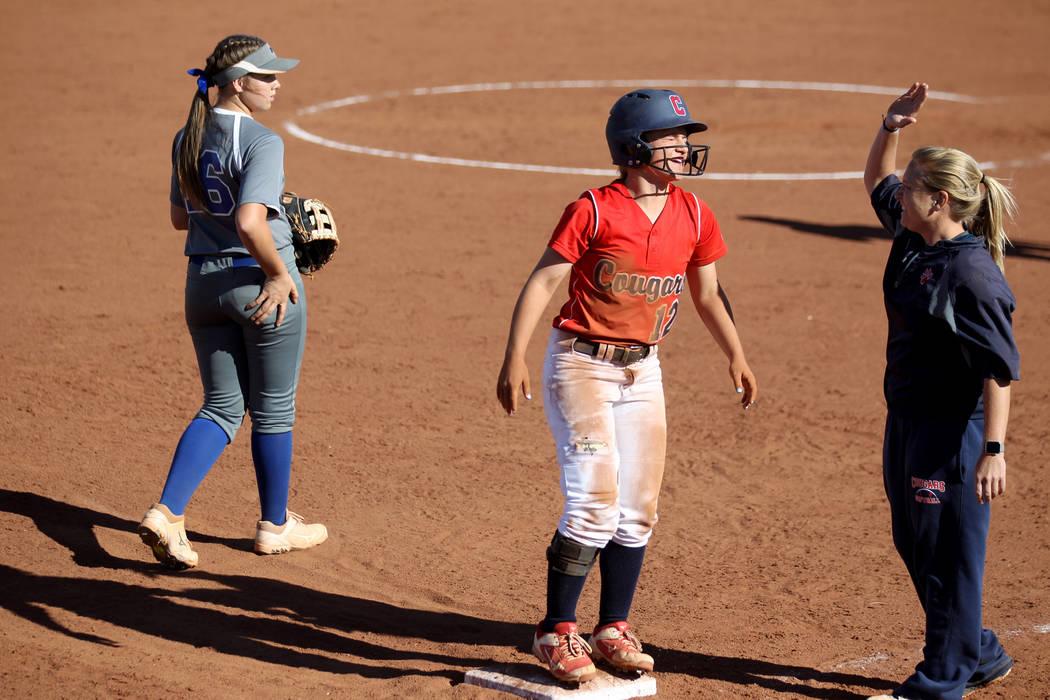 Coronado baserunner Paige Sinicki (12) gets a high five from coach Melissa Krueger on third bas ...