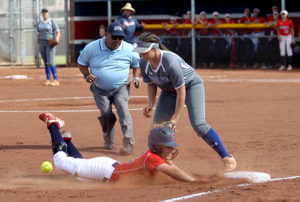 Coronado baserunner Paige Sinicki (12) slides safely into third base as Basic Madison Berg (16) ...