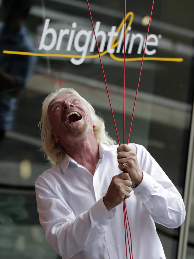Richard Branson, of Virgin Group, prepares to unfurl a banner during a naming ceremony for the ...