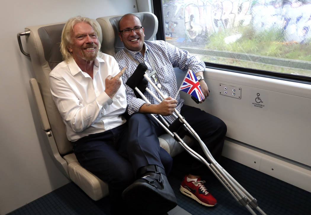 Richard Branson, of Virgin Group, left, sits with a passenger while riding a Brightline train f ...