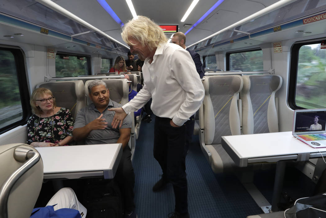 Richard Branson, of Virgin Group, center, greets a passenger while riding a Brightline train fr ...