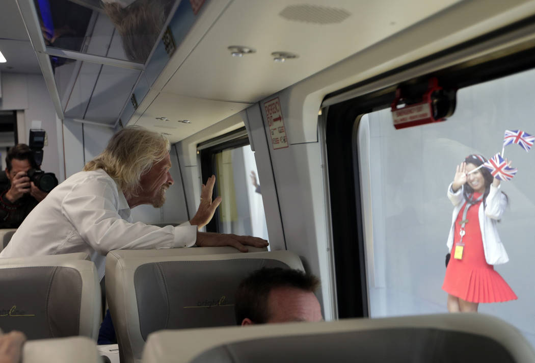An employee holding British flags waves as Richard Branson, of Virgin Group, left, departs on a ...