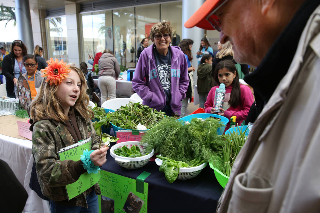 Goynes Elementary School student Juliet Robertson, 10, offers samples of mint leaf to customers ...