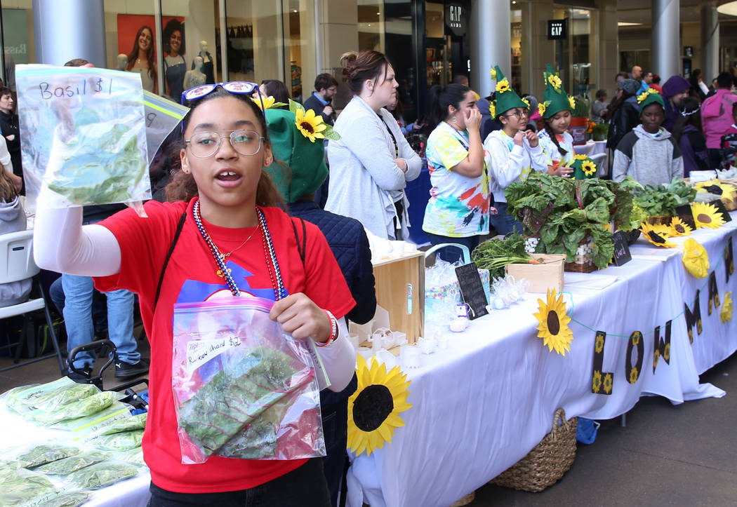 J.E. Manch Elementary School student Miasia Sanders, 11, displays basil and rainbow chard at G ...