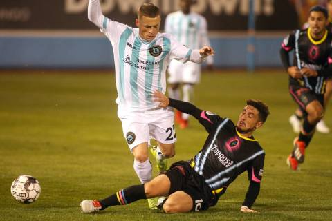 Las Vegas Lights FC midfileder Lucas Scaglia (16) slides into Austin Bold FC forward Clayton Ad ...