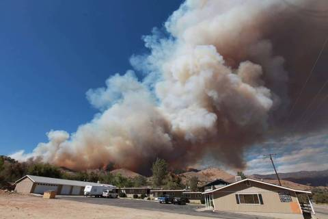 In this Monday, Aug. 18, 2014, file photo, smoke rises from a fire in Wofford Heights, Calif. T ...