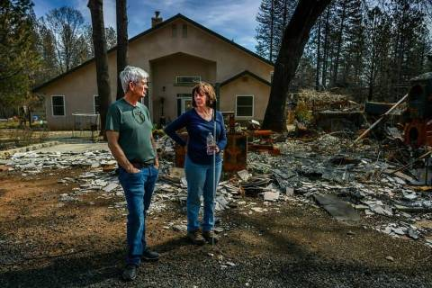 In this March 19, 2019 photo, Oney and Donna Carrell stand near the ashes of her father's house ...