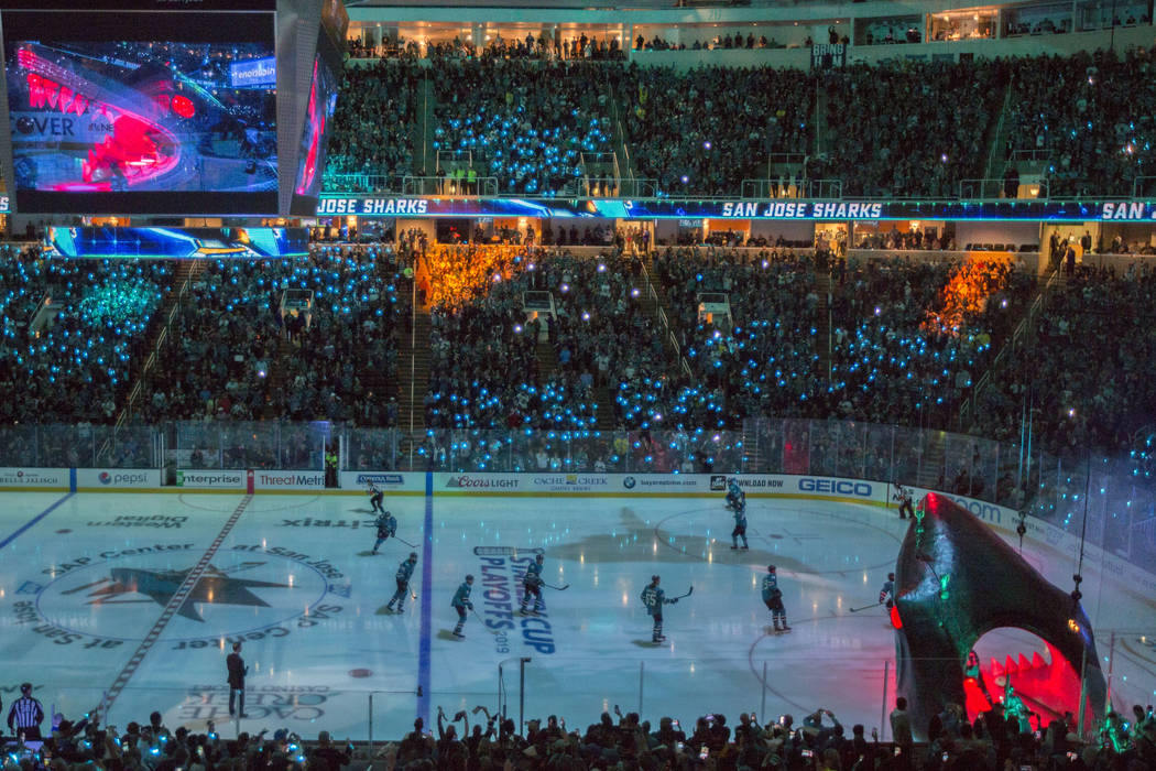San Jose players circle the ice after entering through a massive shark head, right/bottom, at S ...