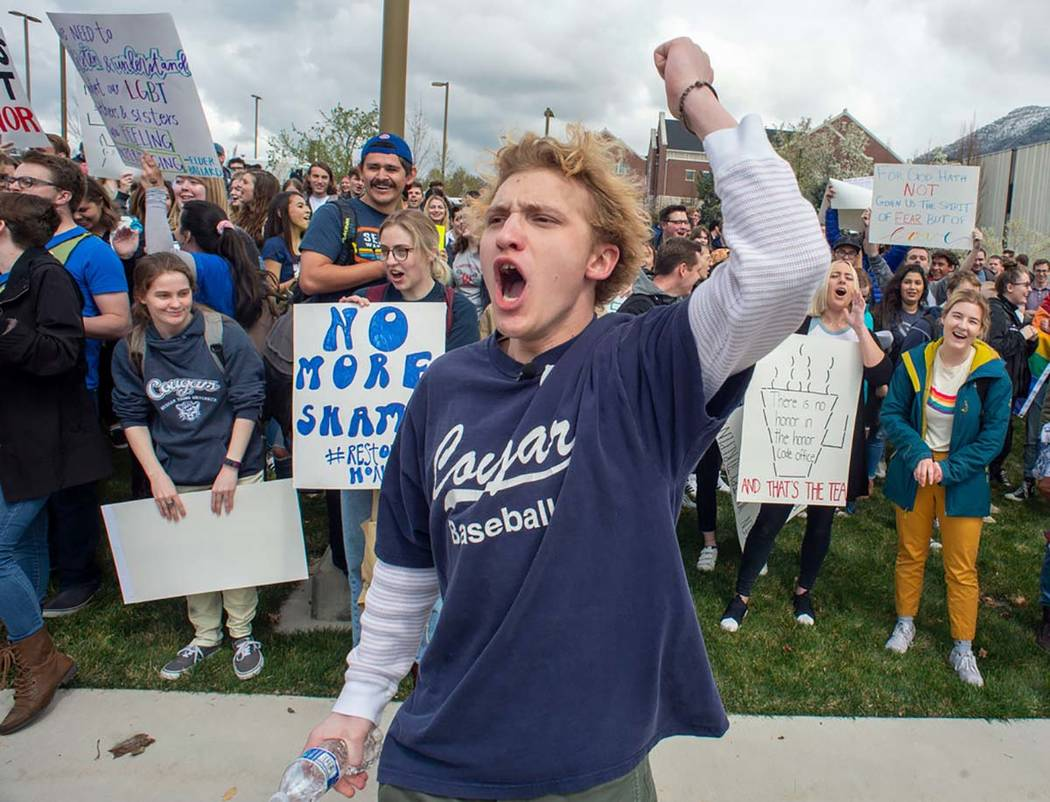Grant Frazier leads a chant as hundreds of students on the campus of Brigham Young University g ...