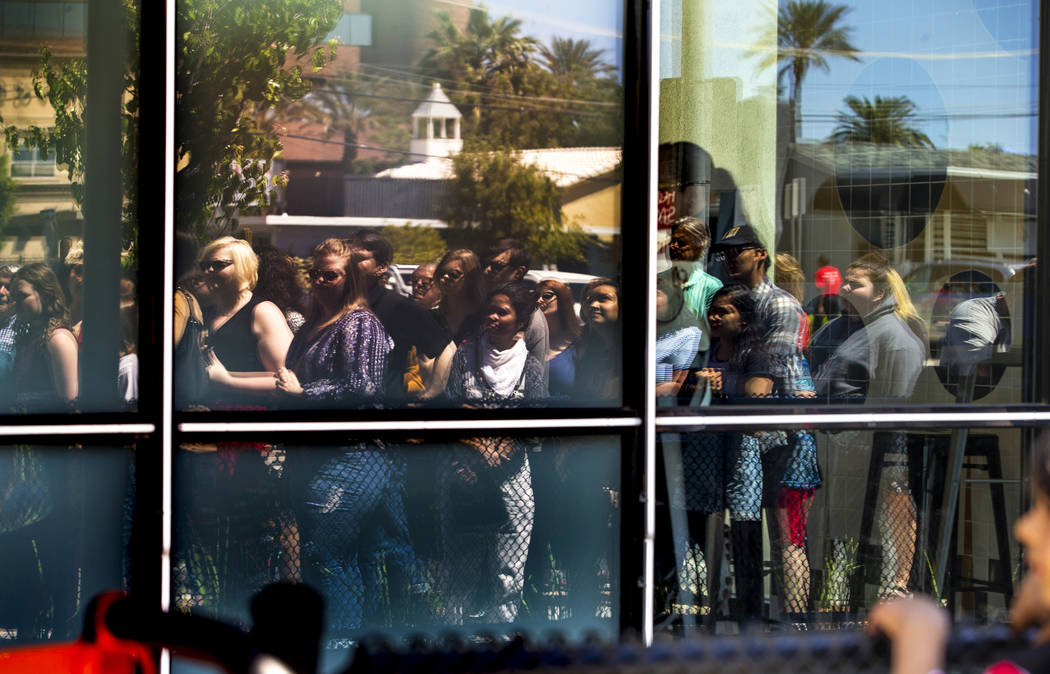 Many patrons reflected in the glass join in on the celebrations during the launch of The Lucy a ...