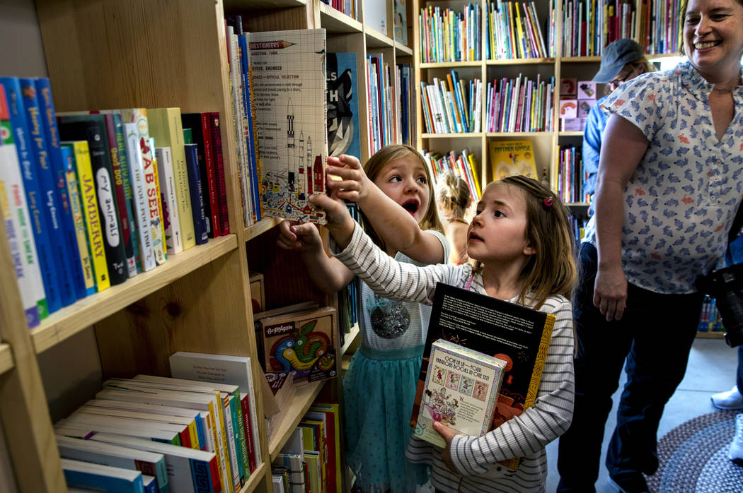 Greta Henderson, 7, and a friend check out all the great books for sale in the young reader's s ...