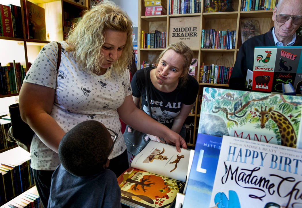 Matthew Graham, 6, Mallory Cyr and Zoe Terry emulate a chipmunk with full cheeks from a book du ...