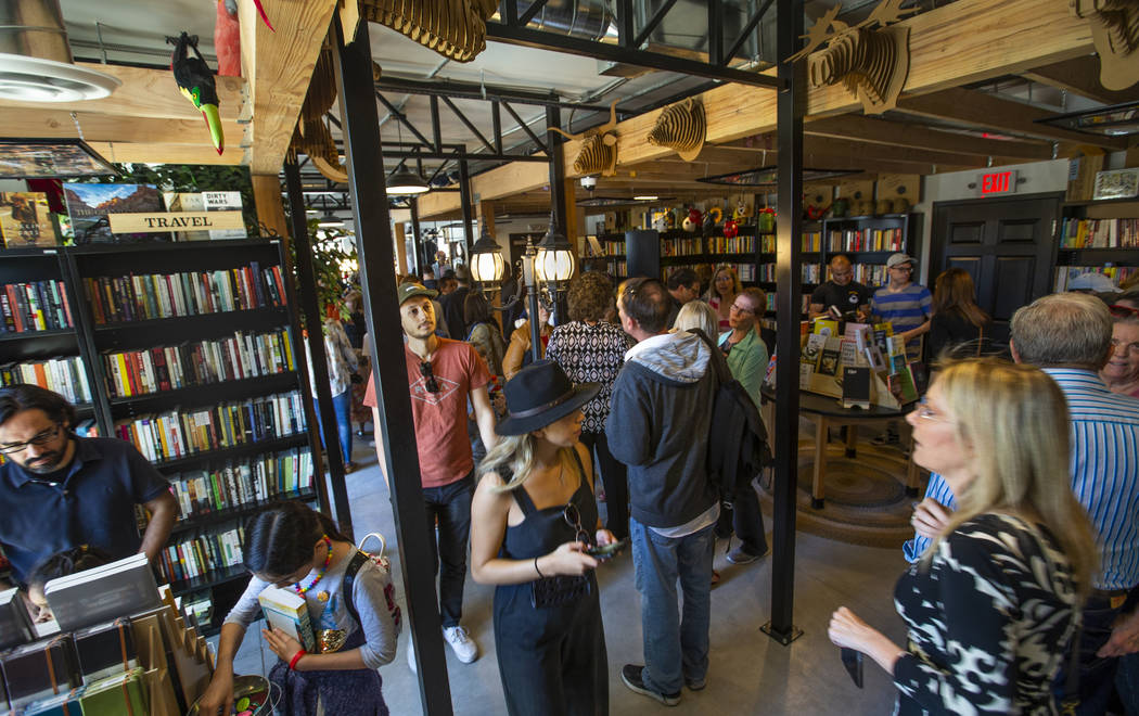 Guests explore all the new sections, books and merchandise for sale during the grand opening of ...