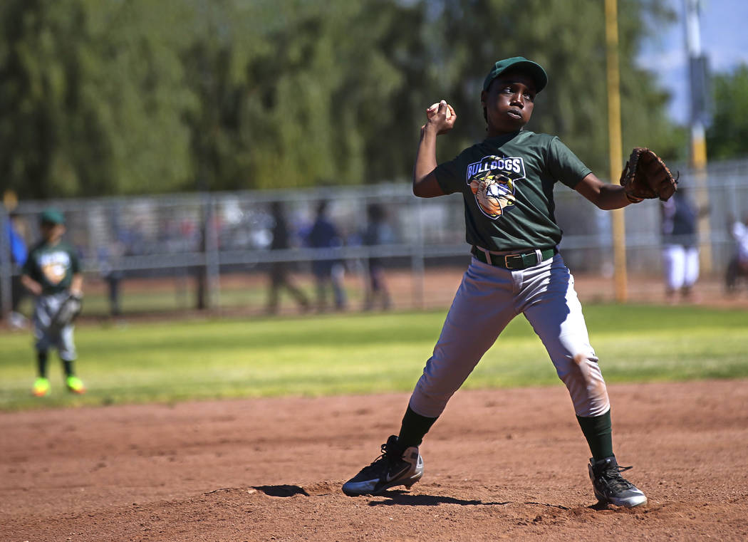 Bulldogs pitcher Marcel Elzy, 12, throws to the Rangers during the opening day celebration for ...