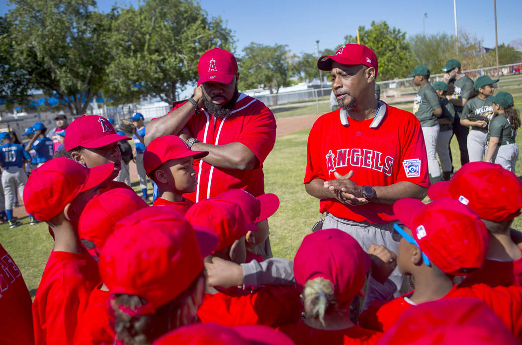 Dale Johnson, coach of the Angels, right, talks with his players during the opening day celebra ...