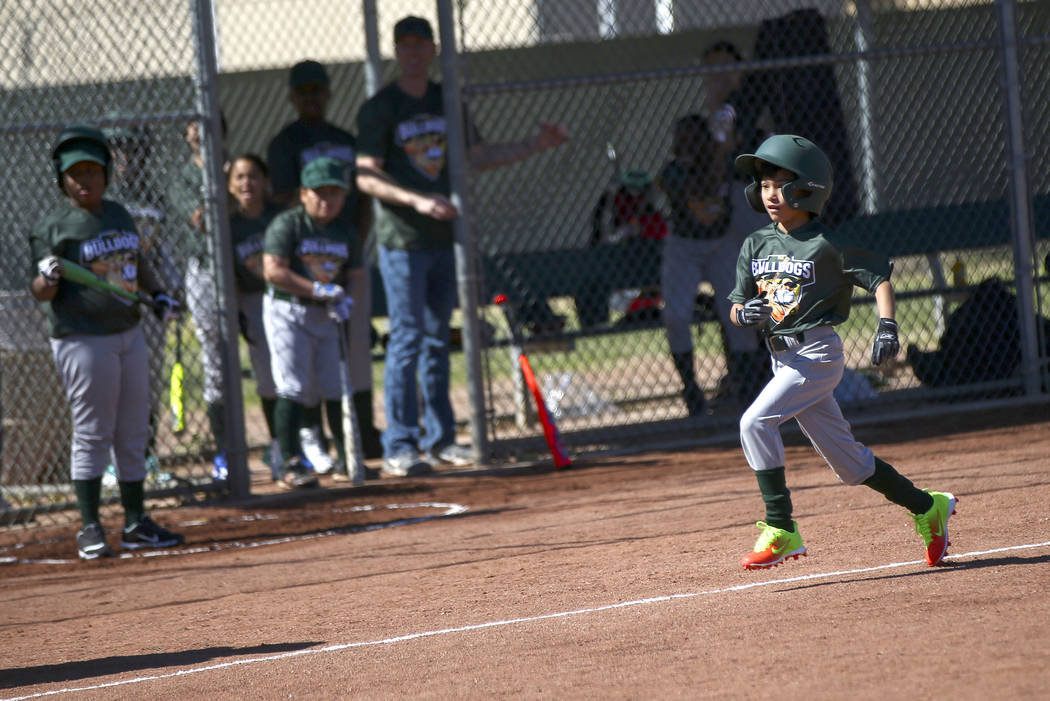 Bulldogs' Nathan Pineda, 9, heads to home plate to score a run against the Rangers during the o ...