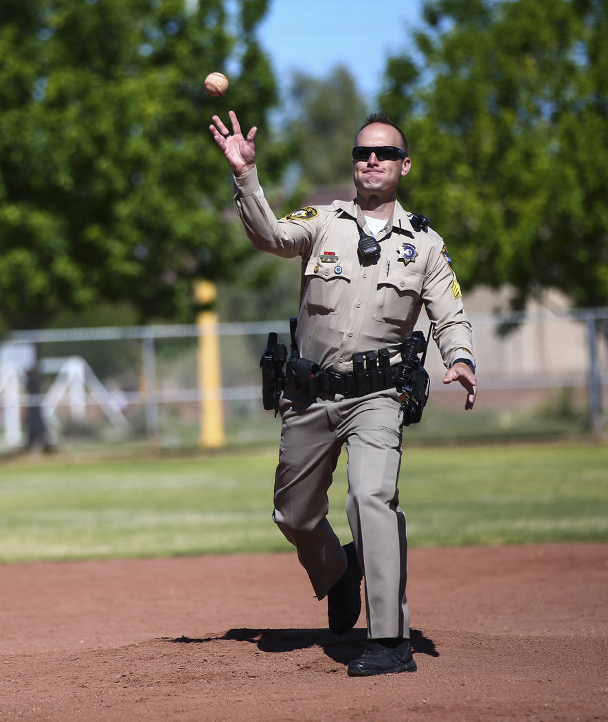 Las Vegas police Sgt. Joshua Stark throws the first pitch during the opening day celebration fo ...