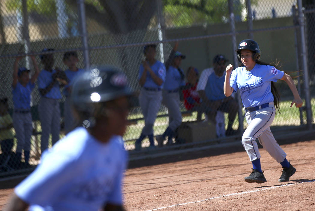 Royals' Natalia Zuniga heads for home plate to score against the Rockies during the opening day ...