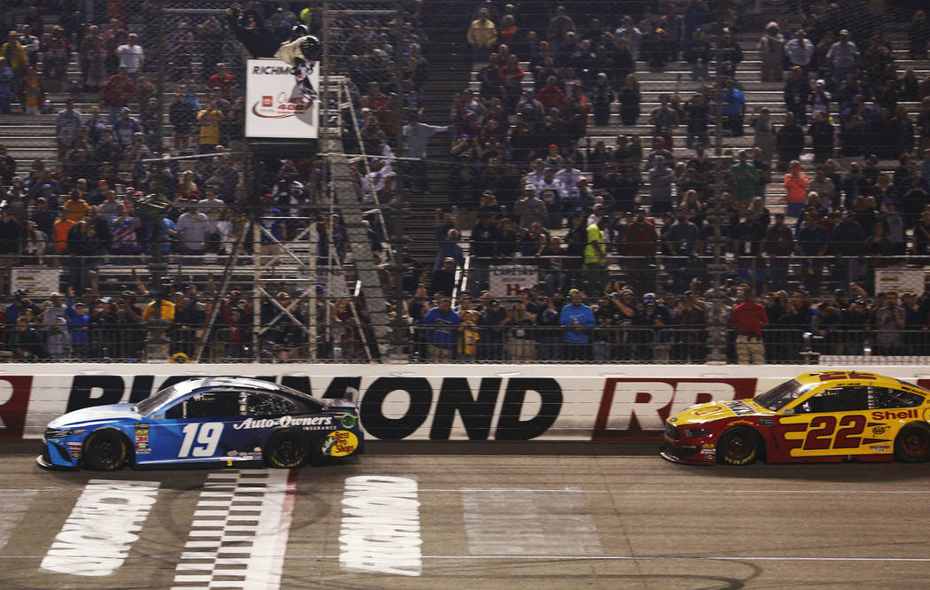 Martin Truex Jr. (19) crosses the finish line in front of Joey Logano (22) to win the NASCAR Cu ...