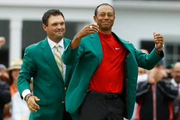 Patrick Reed helps Tiger Woods with his green jacket after Woods won the Masters golf tournamen ...