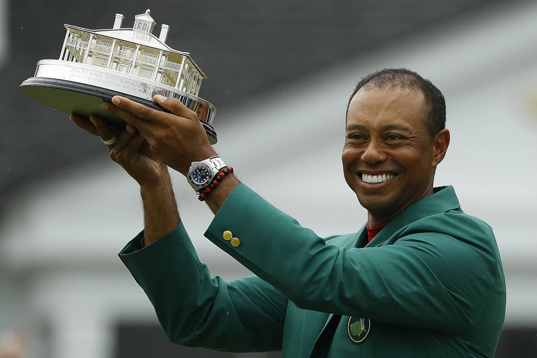 Tiger Woods wears his green jacket holding the winning trophy after the final round for the Mas ...