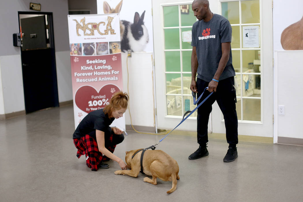 Foster Coordinator Shelby Haycock pets Gunner next to Kettle Manager Dwane Crawford at the Neva ...