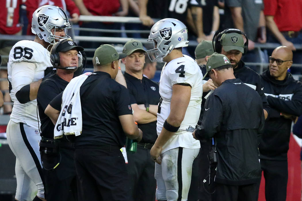 Oakland Raiders head coach Jon Gruden and quarterback Derek Carr (4) have a conversation as tig ...