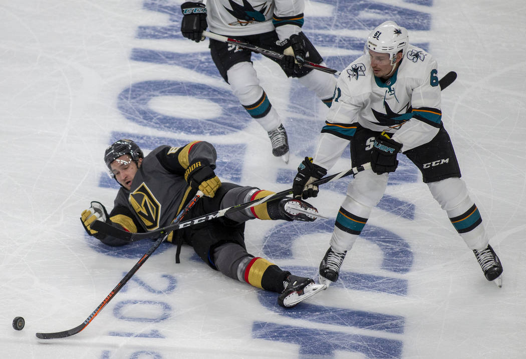 Golden Knights right wing Mark Stone (61) is taken down to the ice with San Jose Sharks defense ...