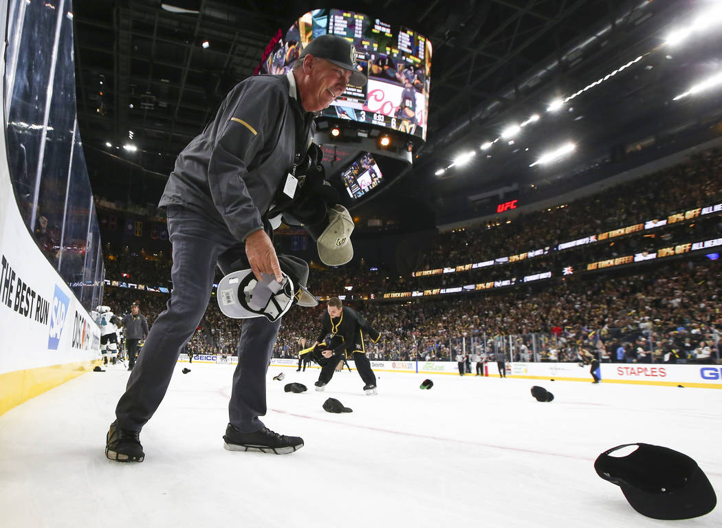Members of the ice crew pickup hats thrown onto the ice as the Golden Knights celebrate a hat t ...